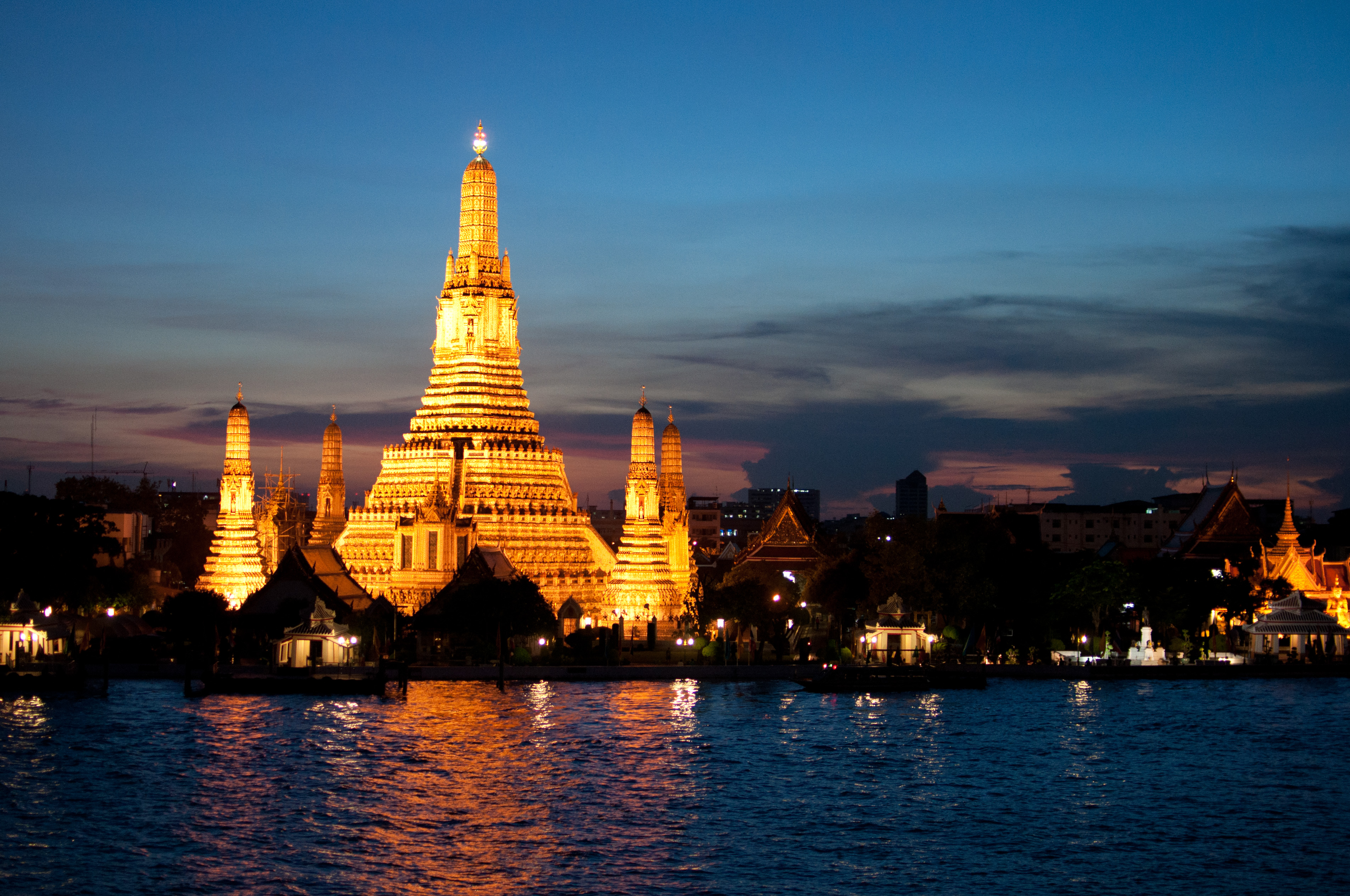 Wat Arun, the Temple of the Dawn, shines across the Chao Phraya River in Bangkok, Thailand.