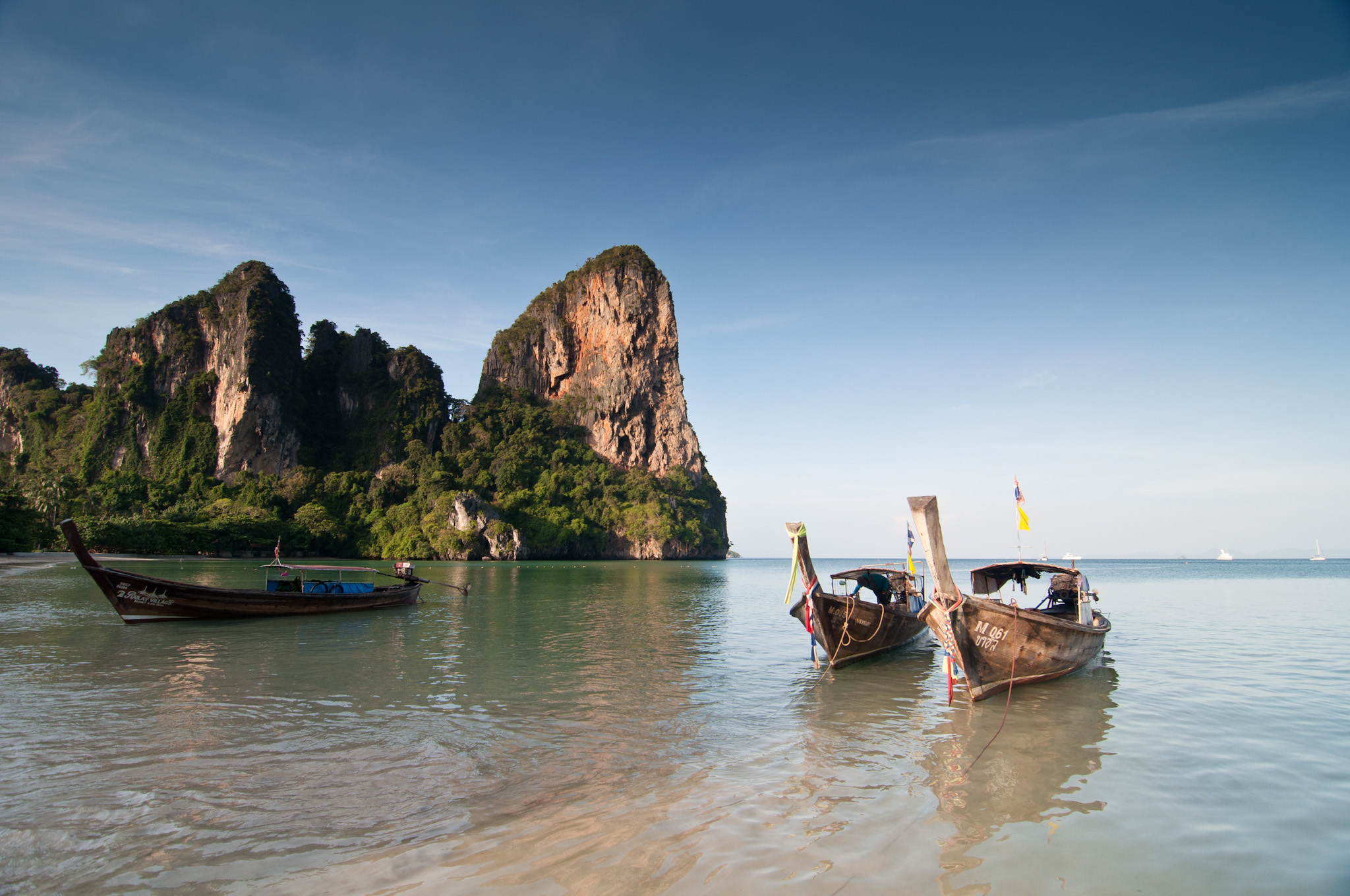The early morning sun bathes the karst (rock formation) behind a long-tail boat at Railay West Beach in Krabi, Thailand.